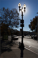 Its graceful lines marred by signs,  an ornate lamp post stands, backlit, its globes glowing with sunlight and a sunburst shining through the opening in the ironwork.  Oakland, California.