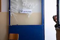 Atene, 17 giugno 2012, elezioni nazionali: la porta di ingresso di un seggio. Un uomo si affaccia all'interno.<br /> Athens, June 17, 2012 national elections, voting<br /> Ath&egrave;nes, Juin 17, 2012 &eacute;lections nationales, les bureaux de vote