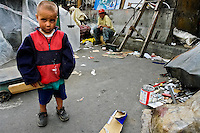 A little Colombian boy plays in the 'Invasión', a temporary slum in Bogota, Colombia, 1 April 2006. The internal armed conflict in Colombia together with lack of social network caused appearence of small invasion slums in all Colombian urban zones in last years. These illegal settlements rise quickly in free uncontrolled spaces between industrial buildings, both in the city centres and peripheries. Shacks do not have sanitation network, neither electricity. Most of their inhabitants are war fugitives violently displaced from their original lands in the country by guerrilla or paramilitary forces. Picking up the rubbish and recycling it is a common survive strategy for people living in these temporal ghettos until those are not dismantled by city administration.