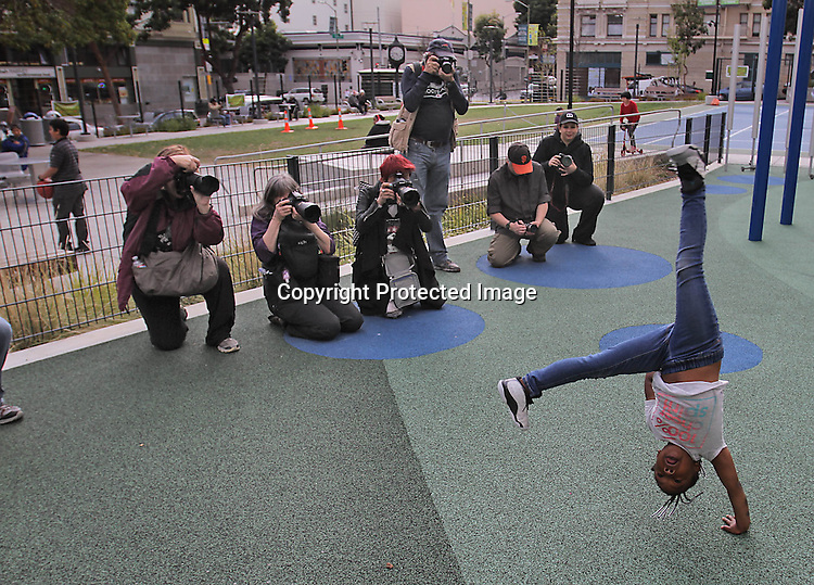 A group of photographers photographed a young girl during chart-wheels in the Tenderloin of San Francisco.