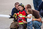 A young boy using a fire hose to spray water with a firefighter and his family