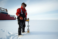 Scientist securing ice cores with a corer that runs off an electric drill, Bering Sea.