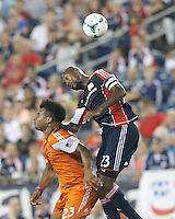 Houston Dynamo midfielder Giles Barnes (23) and New England Revolution defender Jose Goncalves (23) battle for head ball.  In a Major League Soccer (MLS) match, Houston Dynamo (orange) defeated the New England Revolution (blue), 2-1, at Gillette Stadium on July 13, 2013.
