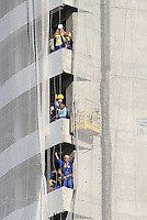Construction workers in a nearby building take time out of their working day to cheer Brazil on during training ahead of tomorrow's World Cup quarter final vs Colombia