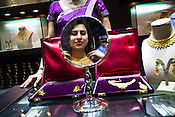 A young woman tries on gold jewelry at a Mehrasons Jewellers store in New Delhi, India. Photo: Sanjit Das/Panos Pictures