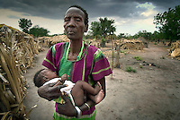 A woman holds her grandchild at a camp for internally displaced persons (IDPs).  She awaits assistance in resettling in Rumbek from humanitarian organisations, having fled the civil war and returned to the area..