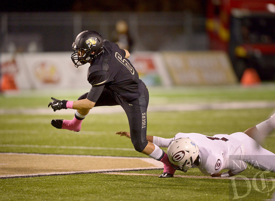 NWA Democrat-Gazette/BEN GOFF @NWABENGOFF<br /> Clay Barganier, Bentonville wide receiver, breaks the tackle of Springdale safety Stone Ben in the second quarter on Friday Oct. 16, 2015 during the game in Bentonville's Tiger Stadium.