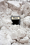 Heavy snow in Madison, Wisconsin covers a outdoor phone booth. .