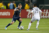 CARSON, CA – May 14, 2011: Sporting KC midfielder Michael Harrington (2) attempts to get past LA Galaxy midfielder Juninho (19) during the match between LA Galaxy and Sporting Kansas City at the Home Depot Center in Carson, California. Final score LA Galaxy 4, Sporting Kansas City 1.