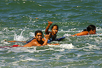 Group of boogie boarders wave the shaka sign while paddling out to the popular surf spot in town called the Bowl.  Ala Moana Oahu, Hawaii.