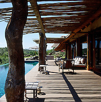 The pool area has a deep wooden deck and a reed pergola and is furnished with a wide daybed and armchairs