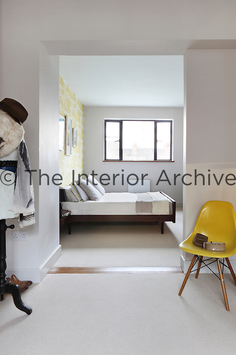 A spacious hallway leads to a guest bedroom decorated with styled simplicity. The yellow of the classic Eames chair is reflected in the artwork and cushions by contemporary artist Michael Papworth.