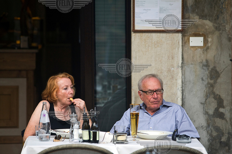 A elderly couple sit at a restaurant table in the Piazza Erbe in Verona, Italy...