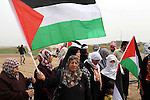 Palestinian women hold up the national flag as he walks across a field during a rally marking Land Day in Beit Hanun in the northern Gaza Strip close to the border with Israel on March 31, 2013. The annual demonstrations mark the deaths of six Arab Israeli protesters at the hands of Israeli police and troops during mass protests in 1976 against plans to confiscate Arab land in the northern Galilee region. Photo by Ashraf Amra