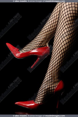 Sexy woman legs in fishnet stockings and red shiny high-heel shoes isolated on black background