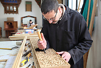 An artisan carving a wooden panel in a workshop in sculpted woodwork at the Artisan School or Dar Sanaa, founded 1919 under the Spanish Protectorate of Morocco, which teaches the traditional art and craft skills of woodwork, zellige, sculpted plaster, leatherwork, etc, in Tetouan on the slopes of Jbel Dersa in the Rif Mountains of Northern Morocco. Tetouan was of particular importance in the Islamic period from the 8th century, when it served as the main point of contact between Morocco and Andalusia. After the Reconquest, the town was rebuilt by Andalusian refugees who had been expelled by the Spanish. Picture by Manuel Cohen