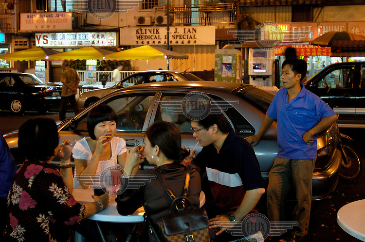 Chinese eating at outdoor tables at a mostly Chinese night food market on Jalan Alor in the Golden Triangle.