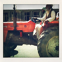 Two men ride a tractor along a Kabul street.