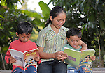 Nob Chan (center) helps her sons with their homework in Khnach, a village in the Kampot region of Cambodia. On the left is Nhouv Kosal, age 7. On the right is Nhouv Visal, age 6.
