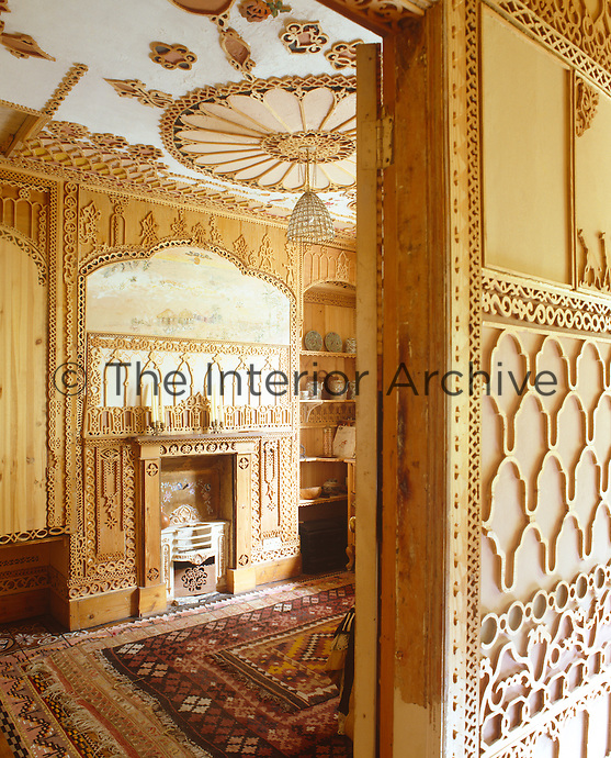 The fireplace in the spare bedroom has a carved wooden surround and ornate fretwork shelves which house a collection of china.