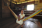 Smiling girl in dress on hammock in her home in Midway Village, southern Belize.<br /> A traditional Mayan village.