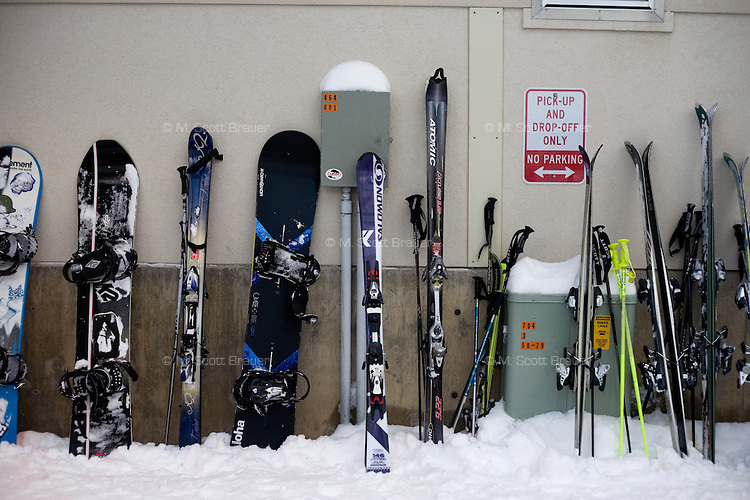 Skis, ski poles, and snowboards rest against a wall of the lodge at Showdown Ski Area on King's Hill in the Little Belt Mountains near Neihart, Montana, USA.