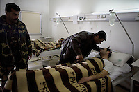 Security forces visit their comrades lying in the military hospital in Damascus, just a few kilometers from fighting in the suburbs. Government forces have suffered many casualties in the last few days. Protests against the ruling Baathist regime erupted in March 2011 and although they were peaceful government forces violently repressed them. In response to being commanded to shoot unarmed civilians large numbers of men deserted the army and formed the Free Syrian Army and an armed uprising began with major clashes taking place in early 2012.