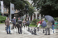 Local men playing giant chess in the square near the orthodox church, in Sarajevo, Bosnia and Herzegovina. The city was founded by the Ottomans in 1461. Picture by Manuel Cohen