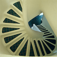 View looking down a whitewashed concrete staircase with steps of blue tiles