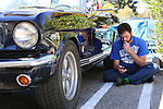 A car owner relaxes beside his dad's car during the Los Altos Fall Festival.