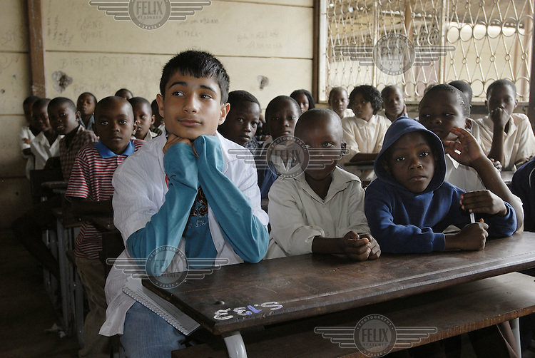 British student education campaigner Jenade Sharma (L) attends a lesson with students at Forces Primary School during the 'Every child needs a teacher' campaign.  He is visiting Mozambique as part of a cultural exchange to urge political leaders to provide education for all children in developing countries..