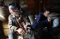 Local men smoke in their home in a small village in Pingwu County in Sichuan Province, south-west China.