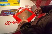 "A visitor plays with an Etch-A-Sketch in the Target ""Wonderland!"" pop-up store in the Meatpacking District in New York on its grand opening day, Wednesday, December 9, 2015. According to Target the store combines physical and digital shopping using medallions given to visitors with an embedded RFID chip. Tapping the chip to an antenna near the product lets you order it. The store is an experiment in technology replacing shopping carts with chips.  (© Richard B. Levine)"