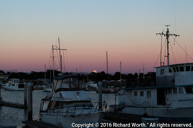 The Full Buck Moon rising over the distant East Bay Hills with boats in the San Leandro Marina in the foreground at the same moment the sun is setting in the west.