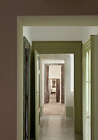 A long corridor has been painted in Verde Chiesuola, a subtle, muted shade of green
