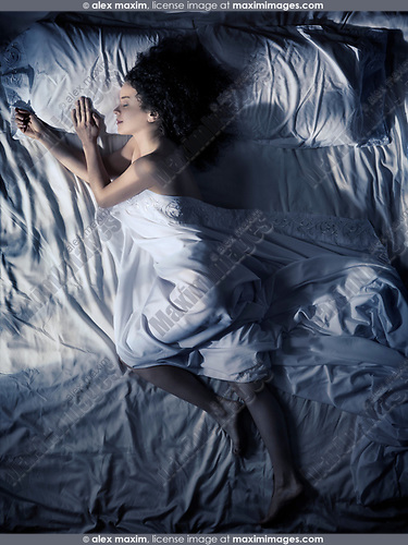 Artistic photo of a young woman sleeping alone in bed on her side at night in dark bedroom lit by moonlight overhead view