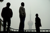 Men on a pedestrian overpass, with the Oriental Pearl TV Tower coming out of a grim pollution laden haze behind.