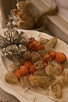 Dried flowers on a creamware plate share a console table with a stuffed squirrel in the kitchen