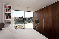 In this contemporary London bedroom a glass wall with sliding doors opens onto a decked balcony