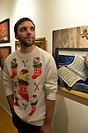BRANDON PETERSON is wearing a festive funny sweater decorated with cats in Christmas stockings, at the Jingle Boom Holiday Bash. There was entertainment, refreshments, and prizes for people wearing the most creative or Ugly Sweaters, at the Main Street Gallery of Huntington Arts Council. Sparkboom, an HAC project, provides events such as this geared to Gen-Y, 18-34 years of age, to address the 'brain drain' of creative young professionals of Long Island. The paintings on the art gallery walls were the Annual Juried Still Life Show.
