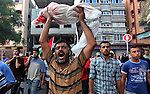 A Palestinian man hold-up the body of one-year-old baby Noha Mesleh, who died of wounds sustained after a UN school in Beit Hanun was hit by an Israeli tank shell, during her funeral in Beit Lahia, northern Gaza Strip, on July 25, 2014. Fifteen people were killed when Israeli fire hit a UN-run school in Gaza, raising the Palestinian toll on the 17th day of the conflict to 777, medics said. Photo by Ashraf Amra