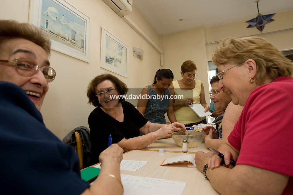 (L-R) Jacqueline Levy, Houria Guita, Kethy Raobelina, Nelly Sayagh, Sylvie Bentolila and Paulette Gelpy laugh together during an Oriental pastry workshop held by the non-profit association Batisseusses de Paix (or Women Peace Builders) that seeks to build ties between Muslim and Jewish women, in a restaurant in Creteil, outside Paris, France, 24 June 2008.