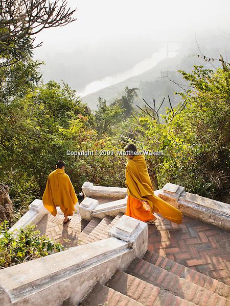 Monks walking down the stairs on the Ban Khamyong side of Mt. Phou Si..Luang Prabang, Laos.