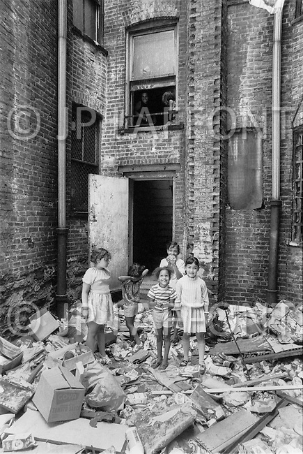Bronx, New York City, NY -  Summer of 1966<br /> Bronx residents volunteer with the removal of trash from their neighborhoods. Children of all ages pitched in to help and play in the rubble.  The Bronx has become the symbol of America&rsquo;s decline.<br /> Bronx, New York City, NY. Et&eacute; 1966.<br /> Le d&eacute;partement des ordures a lanc&eacute; une campagne d&rsquo;un weekend, appelant les habitants &agrave; nettoyer leurs cours et les all&eacute;es. Les enfants en profitent pour jouer &agrave; la chasse au tr&eacute;sor. Le Bronx est le symbole du d&eacute;clin de l&rsquo;Am&eacute;rique.