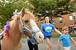 Garden City, New York, U.S. - June 6, 2014 -  A young boy just finished riding a pony at the Garden City Belmont Stakes Festival, celebrating the 146th running of Belmont Stakes at nearby Elmont the next day. There was street festival family fun with live bands, food, and more, and a main sponsor of this Long Island night event was The New York Racing Association Inc.