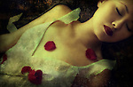 A young Asian woman lying asleep with red rose petals