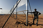 A.G, an Eritrean labourer working for an Israeli construction company, works on the construction of a barrier at Israel-Egypt border, some 70 km north of Eilat, southern Israel. Alarmed by what it described as a near-doubling in the influx of Africans seeking work or claiming refugee status, Israel last year began erecting a fence along the frontier.