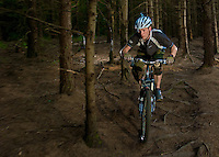 Mountain bikers race downhill in Llantrisant forest in south Wales, UK.