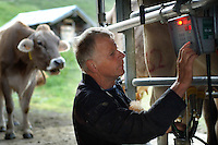 Cowherd and cheesemaker in the portable hi-tech dairy, milking cows.  He spends 100 days in the summer, high up in the mountains, tending cows and pigs and making cheese at Balisalp and Käserstatt near Meiringen, Switzerland.
