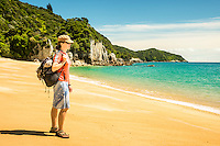 Young woman poses on pristine Anapai Bay on Abel Tasman Coast Track, Abel Tasman National Park, Nelson Region, South Island, New Zealand